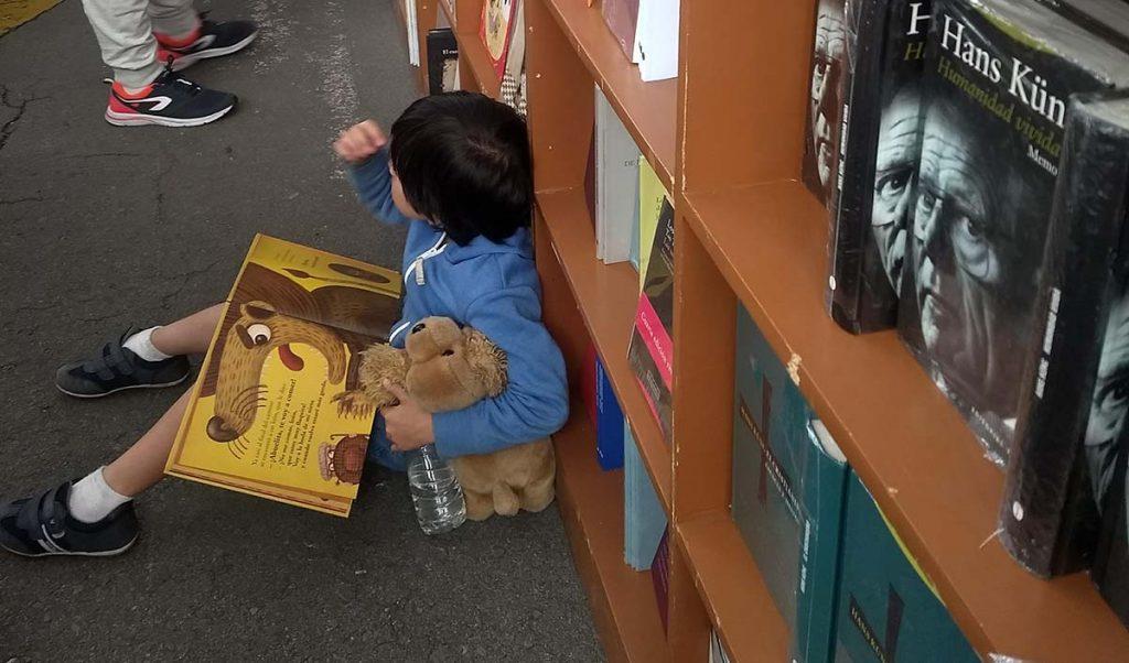 niño leyendo en el piso de un stad de una feria del libro